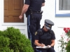 (CAMPBELLFORD 08/15/11) Police knock on doors throughout the neighbourhood where an 82-year-old woman was murdered on the weekend. Photo by Jennifer Bowman