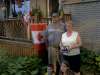 """TRENTON ONT (27/06/2011) Nancy and Karl Reid stand with their step grandchildren Selina and Dalton. Nancy holds a picture of her son Jonathan and her late daughter- in- law Andrea. The Reids fly a permanent Canadian flag, but the the temporary flags have a lot more meaning. They are put out in honour of Andrea who became a Canadian citizen on Canada day five years ago. Andrea passed away on May 26 2011 from an infection. """"She loved seeing her flags out on Canada day,"""" said Nancy Reid. """"She thought Canada was the best country on earth,"""" said Karl Reid. Photo by Linda Horn"""