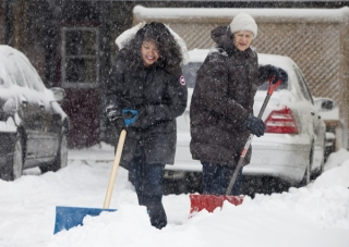 BELLEVILLE, ONT. (13/01/12) — Leticia Siasat gets help from her landlord Helga Hasleuer during the first real snow fall in Belleville this winter. Siasat said her car was practically buried but she didn't mind the snow. Weather reports say there was about 10-15cm by Friday afternoon but more snow continues to fall. (Photo by Kristen Haveman)
