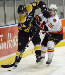 KINGSTON, Ont. (22/01/2012) – Kingston Frontenacs' Andrew Tessier (#44) battles for the puck against Belleville Bulls Stephen Silas (#26) behind the Frontenacs' net during the game Sunday.   Kingston beat Belleville 3-2 at their home game Sunday at the K-Rock Centre.  Photo by Julia McKay