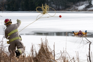 NAPANEE, Ont. (28/01/12) – A member of the Fire Service's Specialized Rescue Team throws a rope to a team member during their annual ice and water training Saturday morning on the Napanee River. Members of the 12 person team went through several drills for the first time this year in order to train four new members and go over past training. The practice seemed increasingly important as just last week, two snowmobilers were rescued from the Bay of Quinte, about a week after the Sophiasburgh ice rescue team did their own training on the water. Photo by Melissa Murray.