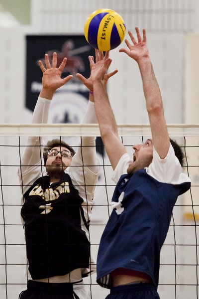 BELLEVILLE, Ont. (14/01/12) — Chris Holden (L) of the Cambrian Golden Shield attempt tries to block the volley of Matt Woods (R) of the Loyalist Lancers during the men's volleyball game against the Loyalist Lancers held at Loyalist College in Belleville, Jan. 14, 2012. The Lancers defeated the Golden Shield 3-0. Photo by Melchizedek Maquiso.