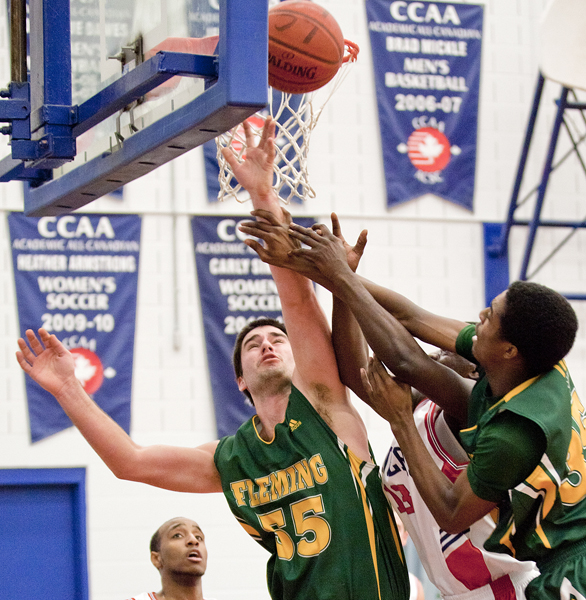 BELLEVILLE, Ont (31/01/12) - Brandon Chambers and Alex Holland of the Fleming Knights and Kevin Owusu of the Loyalist Lancers battle for the rebound during the men's basketball game held at Loyalist College.  The Knights won 79-72.  Photo by Melchizedek Maquiso.