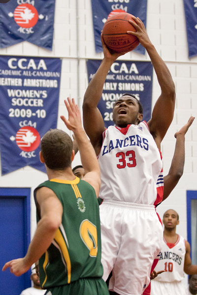 BELLEVILLE, Ont. (31/01/12) - Max Clarkson of the Fleming Knights attempts to block a field goal attempt by Patrick Kalala of the Loyalist Lancers during the  men's basketball game held at Loyalist College.  The Knights won 79-72.  Photo by Melchizedek Maquiso.