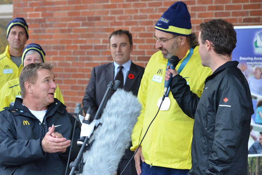 Rick Hansen listens to and applauds medal-bearer Harold Cliff Andrews at a short ceremony at Market Square Monday.  Photo by Taylor Renkema