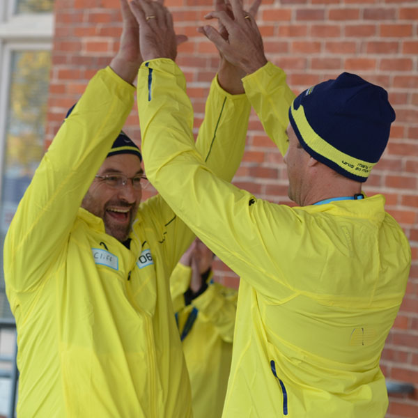 Medal bearers Harold Cliff Andrews and Jeff Lay celebrate with a high five after their leg of the relay at Market Square Monday afternoon. Photo by Taylor Renkema.