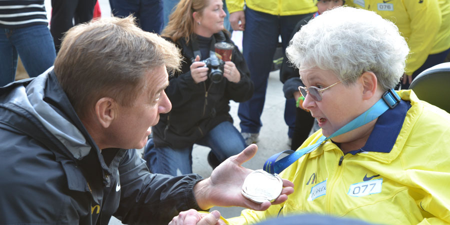 Rick Hansen welcomes final medal bearer Karen Kitchen to the Quinte Sports Center, holding her hand and congratulating her. Photo by Taylor Renkema