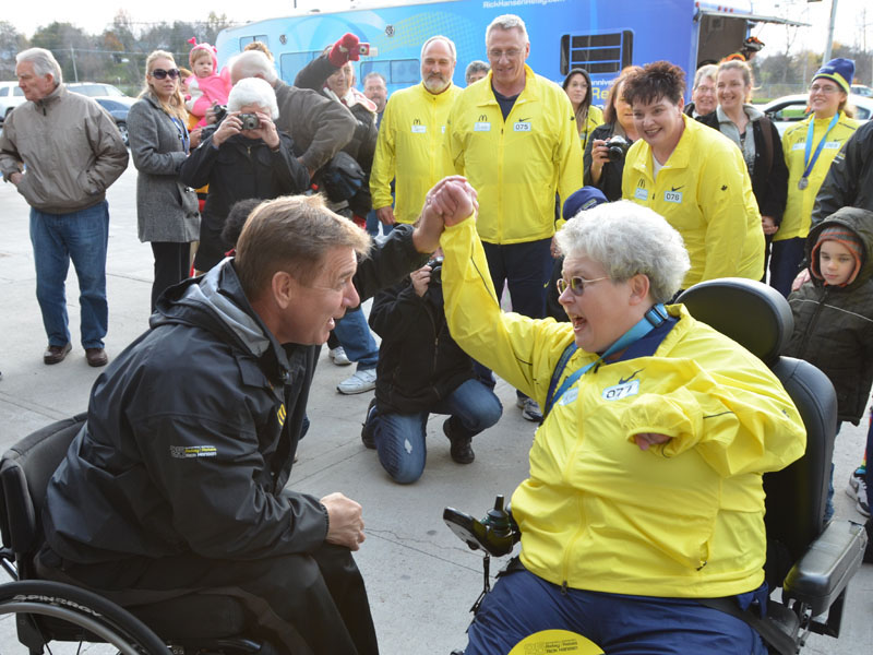 Rick Hansen celebrates the end of the Belleville relay with final medal-bearer Karen Kitchen outside of the Quinte Sports Center. Kitchen was born with Cerebral Palsy, and has dedicated countless hours to making Belleville more accessible.  Photo by Taylor Renkema