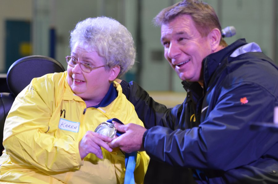 Karen Kitchen and Rick Hansen smile for the cameras with the relay medal on stage at the Quinte Sports Center. Photo by Taylor Renkema