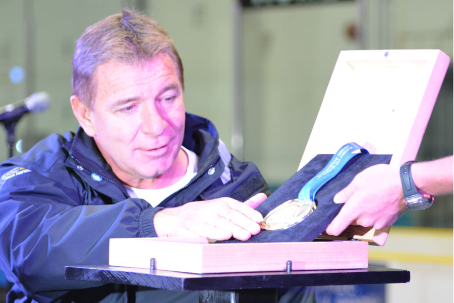 Rick Hansen places a relay medal in a box to mark the end of this leg of the relay.  Photo by Taylor Renkema