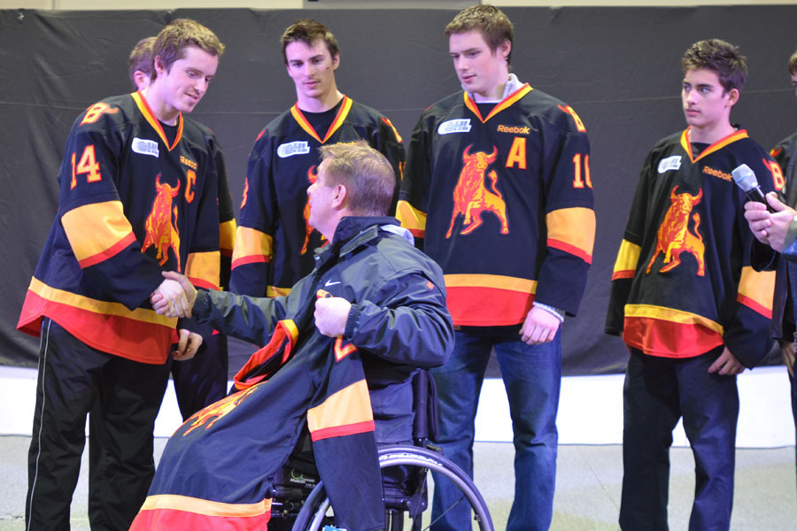 Belleville Bulls captain Juke Judson shakes hands with Rick Hansen after presenting Hansen with his own Bulls jersey while Adam Payerl, Brendan Gaunce and Alex Carnivale look on. Photo by Taylor Renkema