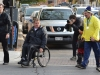 Rick Hansen wheels his way into Market Square surrounded by medal bearer Harold Cliff Andrews, fans and media. Photo by Taylor Renkema