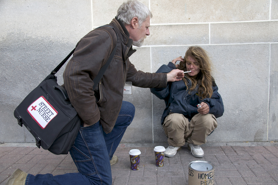 """BELLEVILLE, Ont. (11/11/11)— Street nurse Doug Roy lights a friends cigarette with his own. """"A street nurse is not very well received by conventional health institutes,"""" says Roy. Photo by Brynn Campbell."""