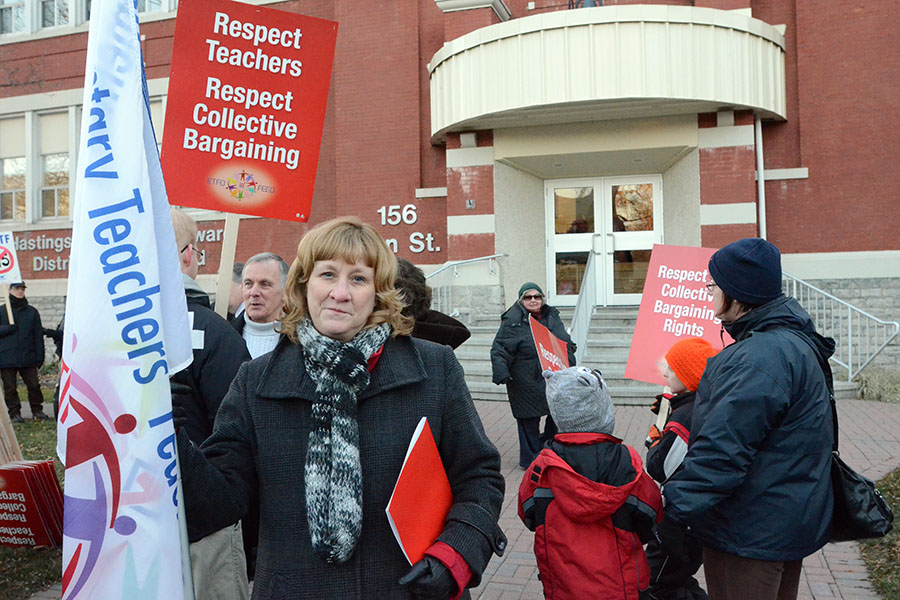 (BELLEVILLE) 11-12-2012 - Karen Fisk, President of the local Elementary Teacher's Federation of Ontario, stands proud with her sign outside the Hastings Prince Edward school board building on Tuesday's rally of solidarity. Photo by Keenan Weaver