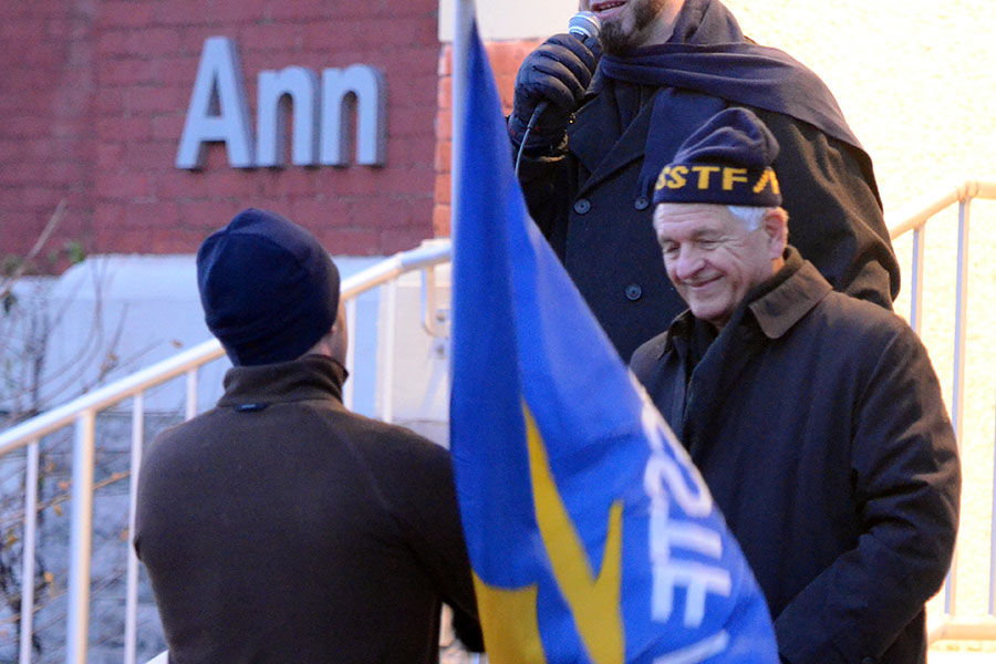 (BELLEVILLE) 11-12-2012 - John Zikopoulos of the OSSTF Active Retired Members happily passes the ceremonial flag of political protest to its new custodian, OSSTF Vice President Keith Sled. Photo by Keenan Weaver