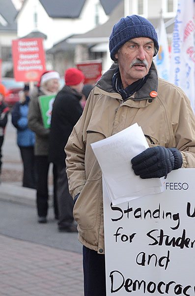 (BELLEVILLE) 11-12-2012 - Michael McMahon, retired teacher and current President of the local NDP Riding Association, overlooks Tuesday's rally at the education center as he passes out papers explaining local plans for battling Bill 115. Photo by Keenan Weaver.