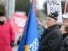 (BELLEVILLE) 11-12-2012 - John Zikopoulos, president of the OSSTF Active Retired Members (ARM) listens intently to Karen Fisk start off Tuesday's rally, bearing a flag that has seen its fair share of political protests. Photo by Keenan Weaver