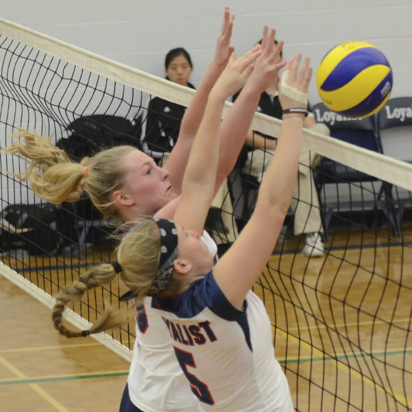Loyalist veterans Kristen Curtis and Kirsten Talsma (5) block the ball in volleyball action Nov. 28. Photo by Taylor Renkema.