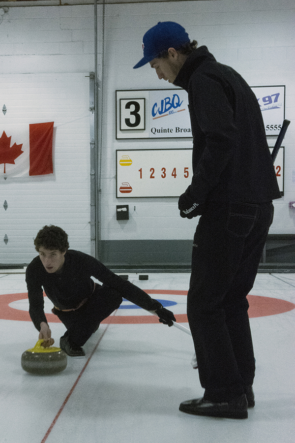 BELLEVILLE, Ont. (01/10/13) Brothers, Mac and Morgan Calwell demonstrate how to properly throw a curling stone at the Quinte Curling Club on Tuesday night. The club opened its sheets to a large group of first time curlers, and with many experienced volunteers coming out to help, everyone was taught the basics.  Photo by Dillan Cools