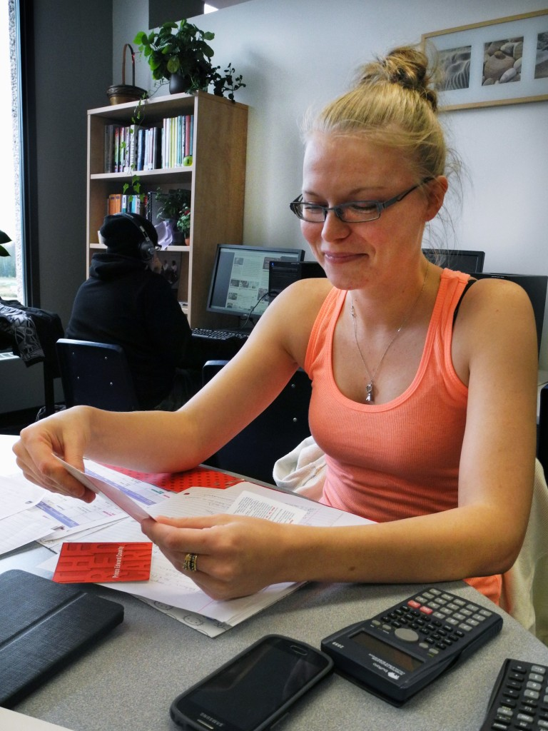 Third-year accounting student Karin Johansen sneaks a peek at this year's Belleville Red Card in Loyalist College's academic skills centre Oct 7.  The project's a product of the Prince Edward Children's Services Network and the Hastings and Prince Edward District School Board.  Photo: Amanda Lorbetski