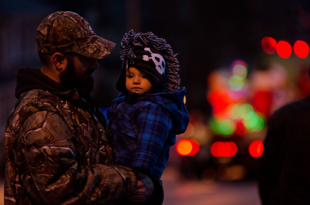 BELLVILLE, Ont (17/11/2013) - Justin Hunter holds Cooper Hunter during the Belleville Santa Claus Parade this past Sunday. The parade saw hundreds of Belleville residents turn out to see Santa Claus, with kids and parents crowding the streets from North Front to Dundas St East, waiting for the man in red. Photo by James Wood
