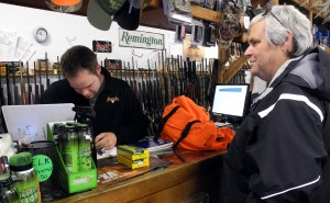 BELLEVILLE- Ben Harvey, manager of Chesher's Outdoor Store, checks a customers firearms license before he makes a sale. Checking licenses before a sale is required by Ontario law. Deer hunting season in the Quinte region started Monday.