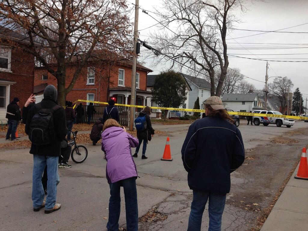 Onlookers have started to gather outside the police tape on Everett Street. Photo by Suzanne Coolen
