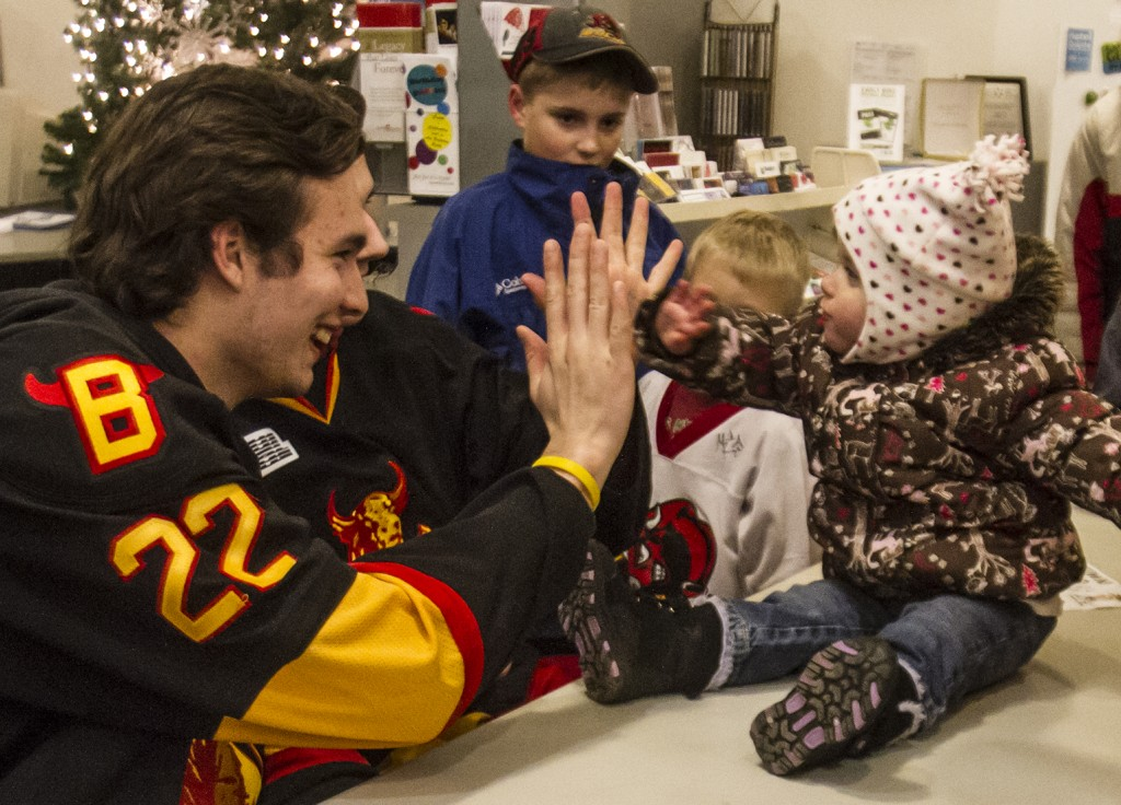 BELLEVILLE- Belleville Bull, Mark Raycroft highfives a toddler at the Quinte Arts Council gallery as a part of the Belleville Bull meet and greet hosted in various locations downtown. Photo by Julia Karpiuk.