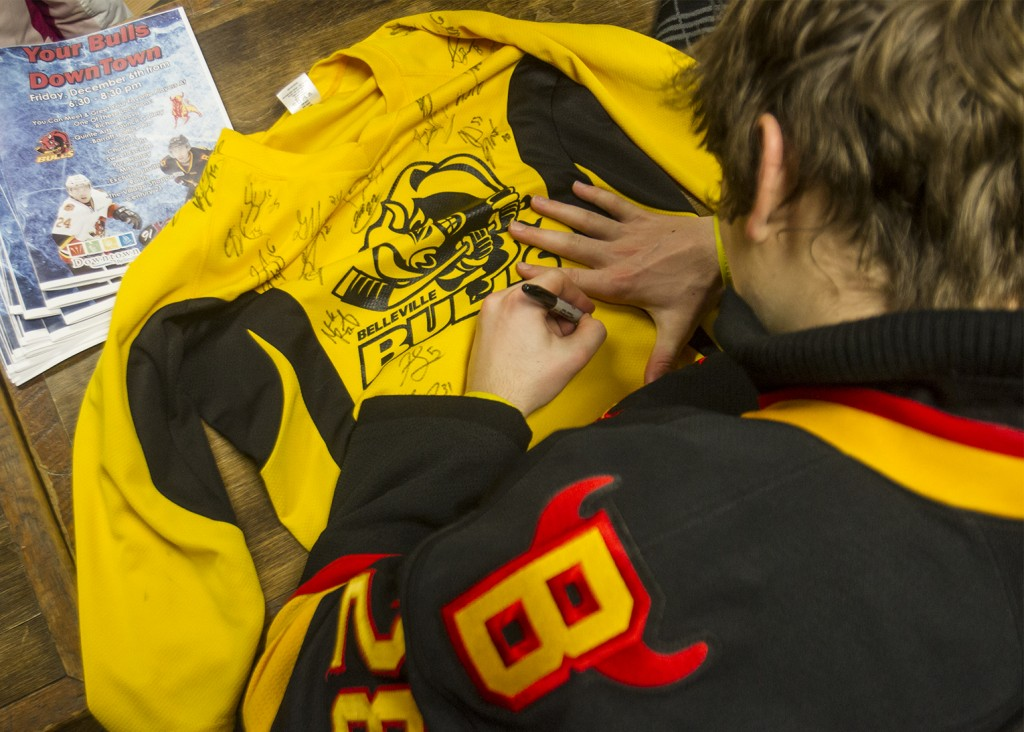 BELLEVILLE- Player David Tomasek signs a jersey for a fan at the Belleville Bull meet and greet hosted in various locations downtown. Photo by Julia Karpiuk.