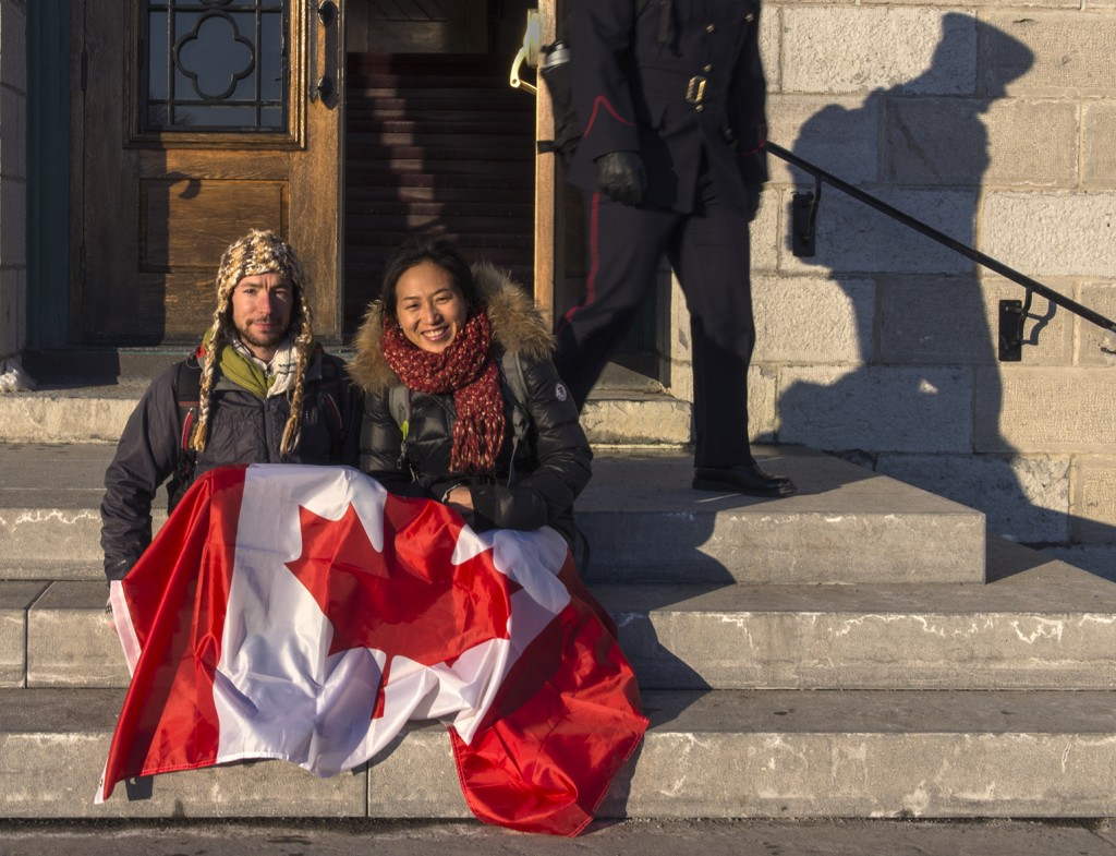 "KINGSTON - Mark Button and his wife Summer Li pose with the Canadian flag on the step of MacKenzie Building at the Royal Military College in Kingston where both are employed as researchers. Originally from the U.K., but having lived in Canada for the last four years, Button is in the final stage of his Permanent Residency application, while Li, from China, was granted permanent residency in 2012, after living in the country for eight years. ""It could be a long and stressful process, but Canada is the best place on earth to live; space, seasons, kind people, beautiful varied landscapes with diversity and tolerance,"" says Button who will know in the next week if he is granted permanent residency. Photo by Guillaume Nolet"