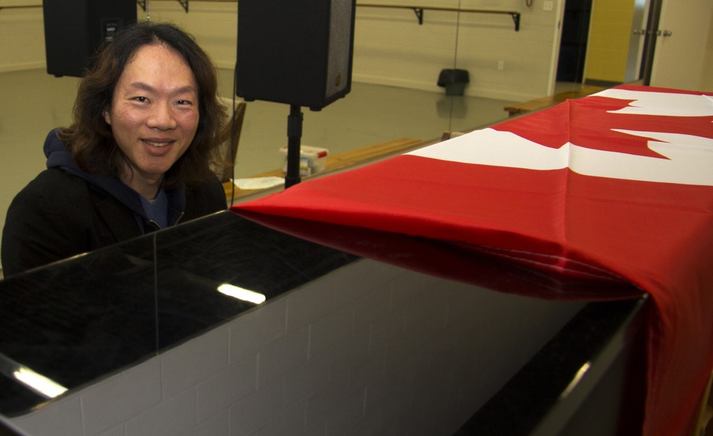 "BELLEVILLE - Hisen Wu poses at his piano at the Quinte Ballet School of Canada. Wu moved to Canada five years ago to be with loved ones, and recently, in Jan., went to Ottawa to become an official Canadian citizen. ""My favorite part about being Canadian is the prosperity,"" says Wu. ""Being here I have more opportunities in my life."" Photo by Samantha Quinn."