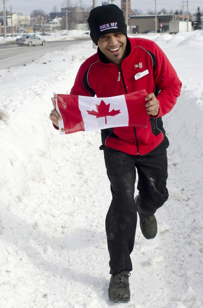 "BELLEVILLE - Holding a Canadian flag againest the wind, Umamg Patel runs along the sidewalk on Dundas Street West. Since coming to Canada three years ago, Patel has grown to love his adopted country, and has applied for permanent residence. He debated moving to the United States, but settled on Canada, because of the ""people being nicer."" Photo by James Wood"