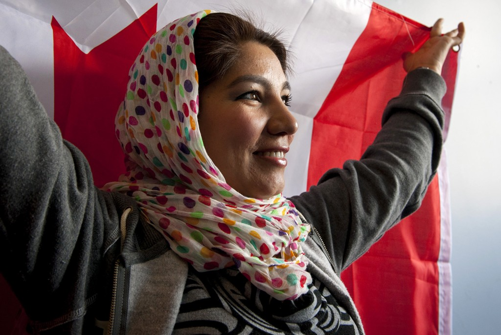 BELLEVILLE, Ont. (12/02/2014) — Farishtah Abdul Jabar, 26, holds up a Canadian flag at her English class in Belleville, Ont. on Wednesday, Feb. 12, 2014. Jabar came to Canda eight months ago from the United States where she had fled from Afghanistan. Jabar was the director of a women's organization in Afghanistan but left because her life was in danger. She is currently a protected person under Canadian law. Photo by Hannah Yoon