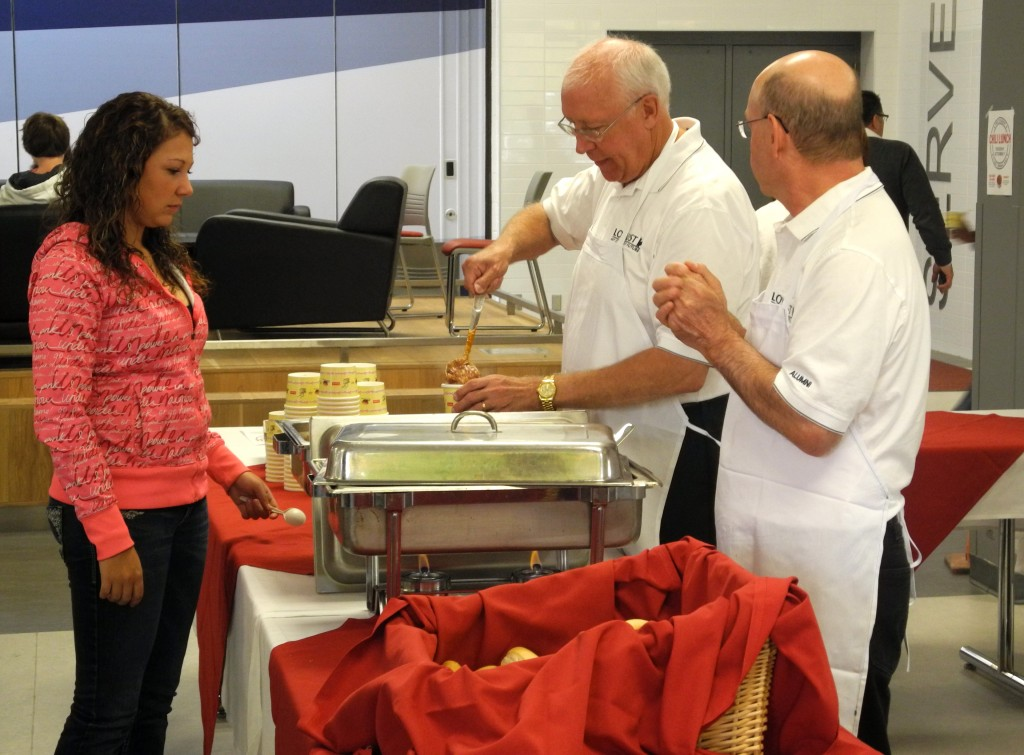Courtney Gautheir, a Loyalist student,  receives a generous portion of chili from George Reddom and Richard Beare, two alumni serving during a special luncheon in the dinning hall Tuesday. Photo by Dylan O'Hagan