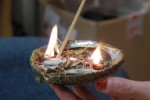 Sarah Michelle Ogden sets the herbs for the smudging ceremony alight. Photo by Joseph Quigley.
