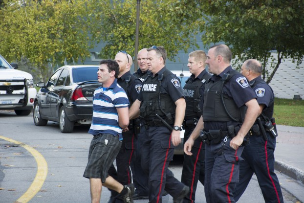 Police take a man into custody following an incident on campus at Loyalist College. Photo by William Acri