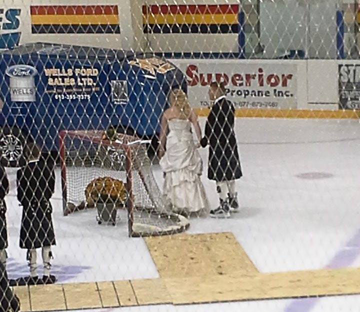 Kelly Sage (left) and new husband Andrew McKracken (right) finish up signing their marriage certificate on-top of the hockey net at the Sterling District Recreational Centre.