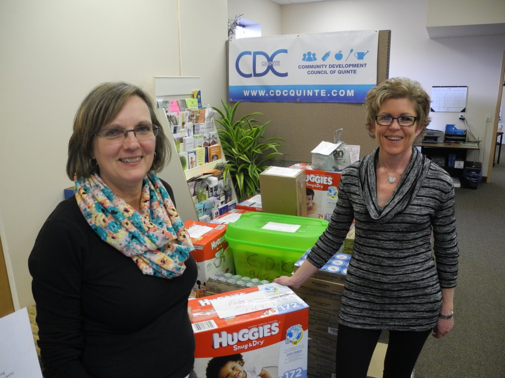 Ruth Ingersoll (left) and Bev Heuving (right) are with the Community Development Council of Quinte.  They're pictured here posing with products packaged to be sent around Hastings and prince Edward County for the Good Baby Box Program, offering baby products to parents for a reduced cost.  Photo by Amanda Lorbetski