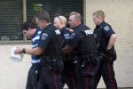 BELLEVILLE, Ont. (07/10/14)— Just after 1 o'clock at Loyalist College, Shane Sabourin was led out of the front doors in handcuffs, after being pepper sprayed. Photo by Hannah Lawson