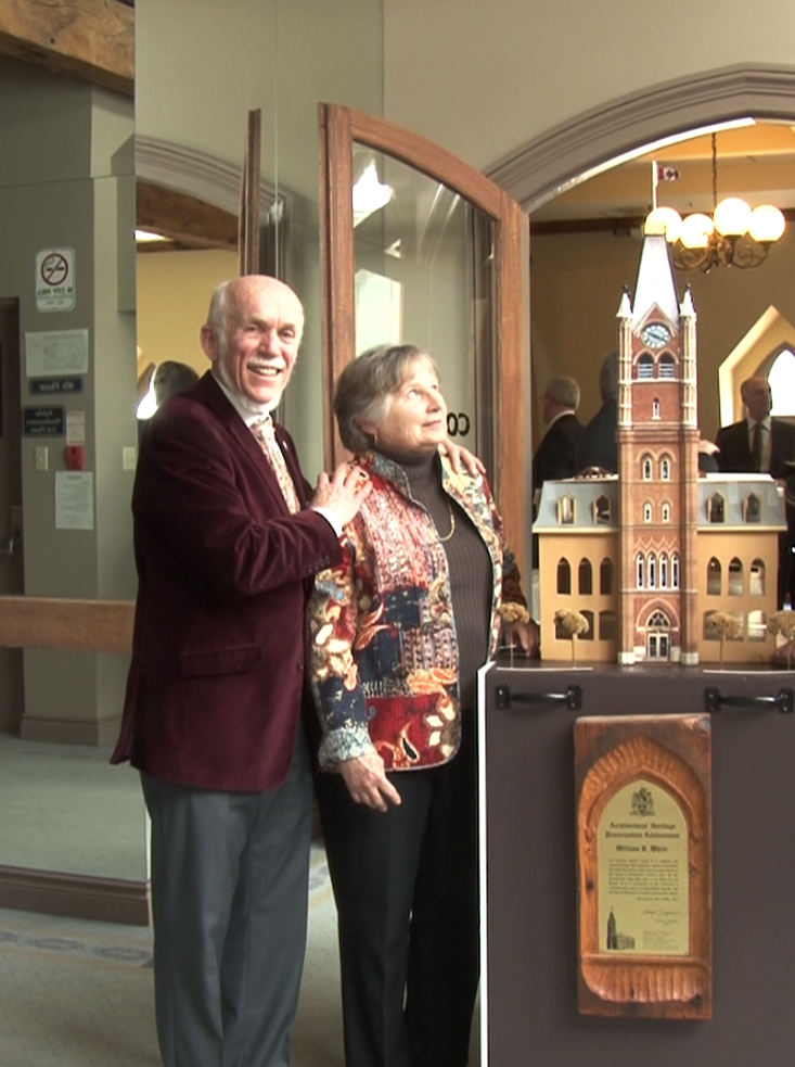 Bill White poses beside his wife Pat and a model of Belleville's city hall. Photo by Cam Kennedy