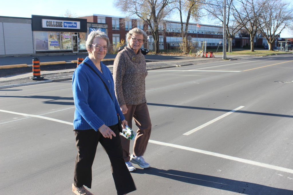 Pat DaSilva (left) and Margaret O'Neil (right) use the newly installed crosswalk on College Street West. The duo have been working, alongside other Amica at Quinte Garden residents to get the crosswalk installed. Photo by Samantha Reed. QNet News.