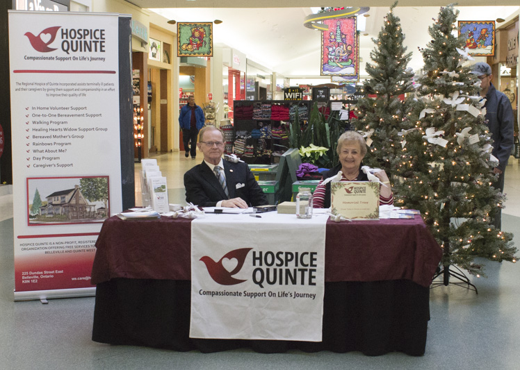 From left, Robert Howell and Helen Mastin sit at the Hospice Quinte memorial tree campaign booth. Howell has been a volunteer for two years, but it was Mastin's first time on the job. She says she looks forward to getting more involved with the organization in the future. Photo by Ashley Clark