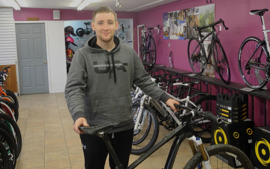Tyler Allsopp stands with his mountain bike at his shop, Doug's Bicycle Sales and Services. Allsopp has spearheaded the proposal for a mountain bike trail through the West Riverside Park. Photo by Joseph Quigley