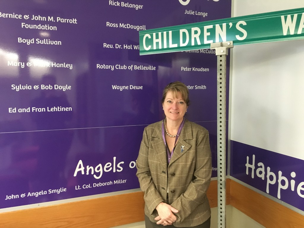 Quinte Children's Foundation executive director Connie Reid in front of the wall that bears the names of all past Guardian Angels Awards winners. Photo by Brock Ormond, QNet News