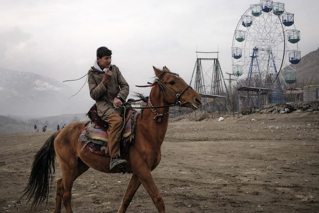 KABUL, Afghanistan (16/01/25) - A boy rides a horse at Qargha Lake, a lakeside resort popular among residents of the city.