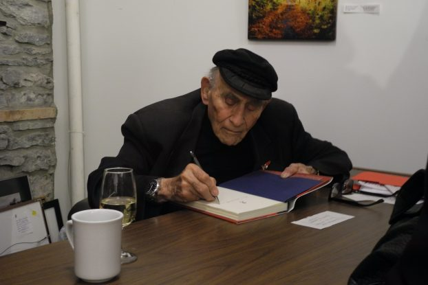 Belleville Author, Peter C/ Newman, signs a copy of his book at The Quinte Arts Council. Photo by Jaykob Story.