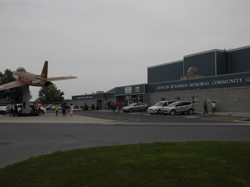 A vintage military jet sits perched out in front of the Duncan McDonald Memorial Community Gardens arena entrance as community members gather around. Photo from Roaming Rinks